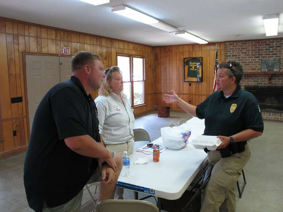 Police Chief Crystal Moore (right) talks with fellow residents of Latta, S.C., last week. Moore returned to work on June 30 after being fired by the small town's mayor in April. Photo: Jeffrey Collins, Associated Press