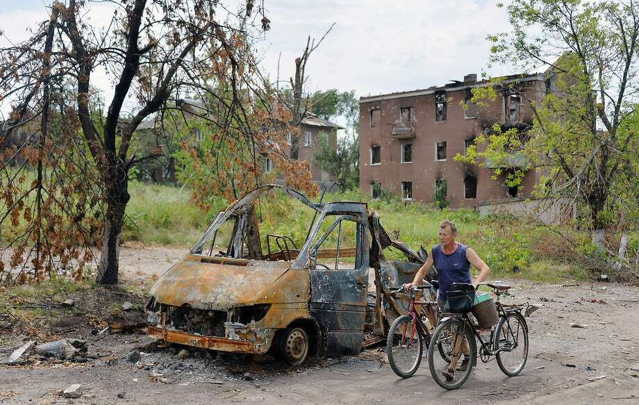 A resident passes a burned vehicle in the village  of Semenovka in the contested Donetsk region. Photo: Genya Savilov, AFP/Getty Images