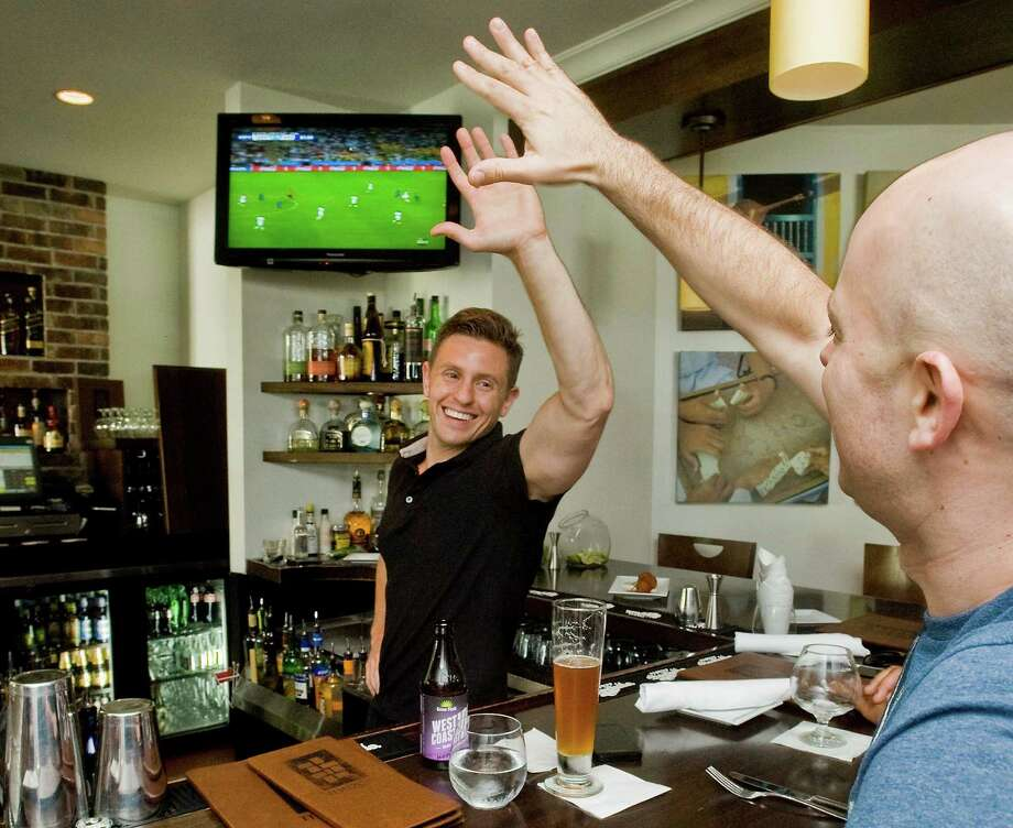 Bartender Keith Maloney high-fives patron Ryan Buzzell of Danbury during the action of the World Cup championship soccer match between Germany and Argentina, at Mezon Tapas Bar & Restaurant on Mill Plain Road in Danbury. Sunday, July 13, 2014 Photo: Scott Mullin / The News-Times Freelance