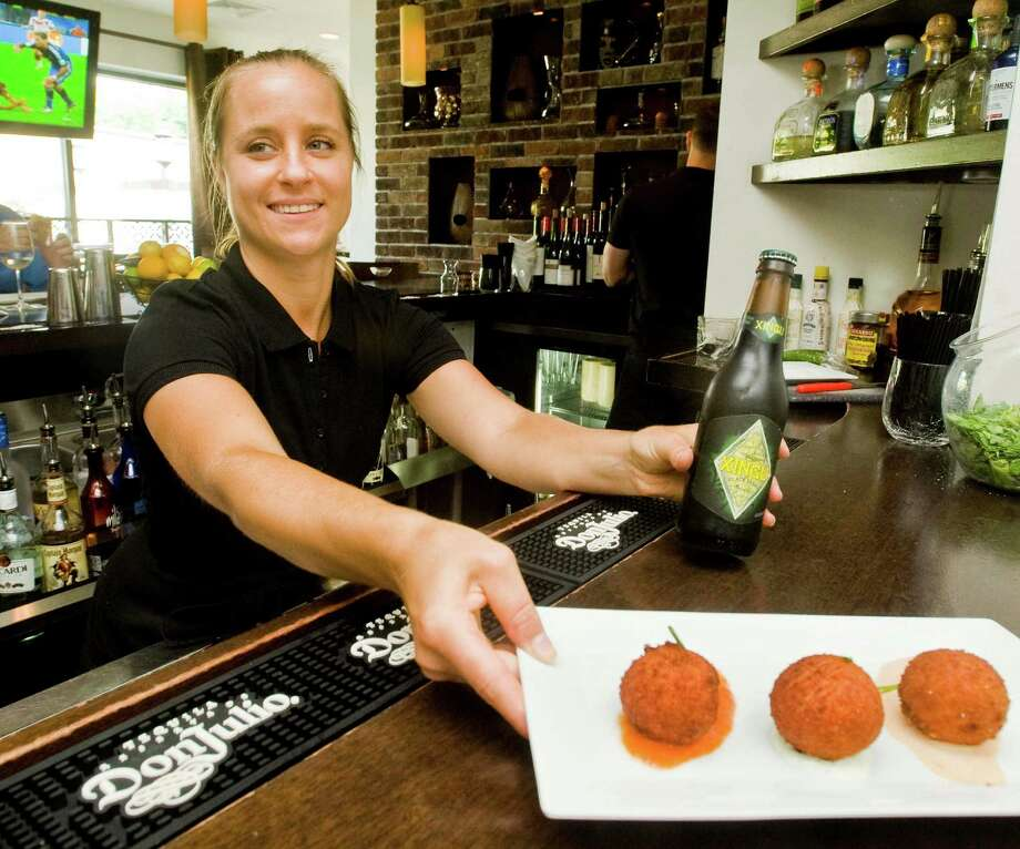 Waitress Jamie Robinson puts out a Coxinhas Brasileiras, shredded chicken dish with Xingu, a black Brazilian beer as a special for the the World Cup championship soccer match between Germany and Argentina, at Mezon Tapas Bar & Restaurant on Mill Plain Road in Danbury. Sunday, July 13, 2014 Photo: Scott Mullin / The News-Times Freelance