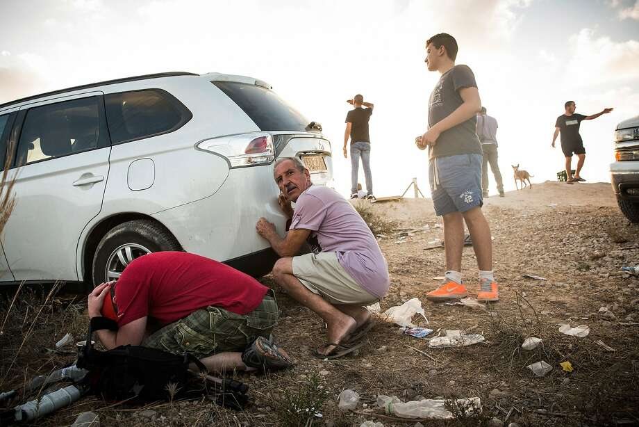 Men take cover behind a car after a rocket attack siren goes off in Sderot, Israel. They were watching air strikes inside the Gaza Strip from the top of a hill on the sixth day of Israel's offensive against Hamas. Photo: Andrew Burton, Getty Images