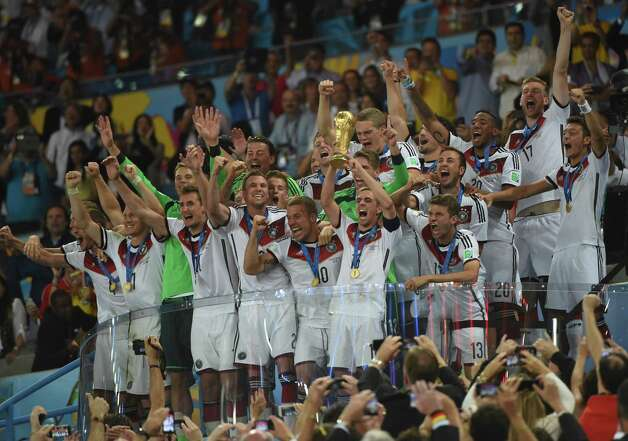 Germany's defender and captain Philipp Lahm (front-2R) holds up the World Cup trophy as he celebrates with his teammates after winning the 2014 FIFA World Cup final football match between Germany and Argentina 1-0 following extra-time at the Maracana Stadium in Rio de Janeiro, Brazil, on July 13, 2014.  AFP PHOTO / PATRIK STOLLARZPATRIK STOLLARZ/AFP/Getty Images Ph