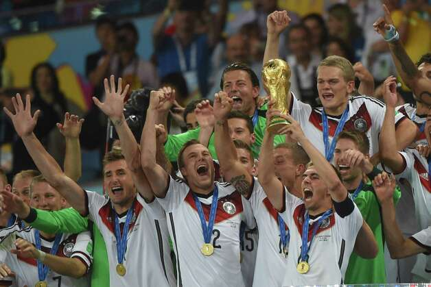 Germany's defender and captain Philipp Lahm (front-R) holds up the World Cup trophy as he celebrates with his teammates after winning the 2014 FIFA World Cup final football match between Germany and Argentina 1-0 following extra-time at the Maracana Stadium in Rio de Janeiro, Brazil, on July 13, 2014.  AFP PHOTO / PATRIK STOLLARZPATRIK STOLLARZ/AFP/Getty Images Photo: PATRIK STOLLARZ, AFP/Getty Images / AFP