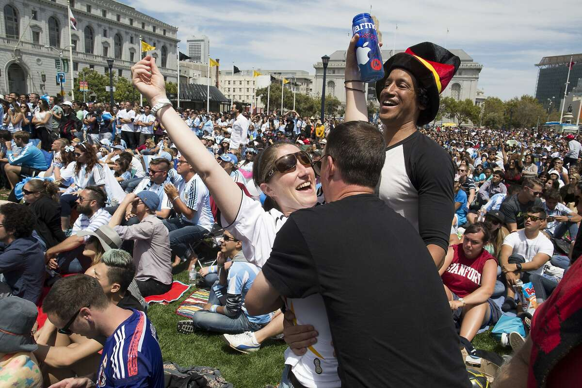 Alec Taylor hugs Julia Schmidt, of Germany, with Efrem Lewis, back right, after Germany scored the only goal in extra time of the Argentina vs. Germany 2014 World Cup finals at Civic Center Plaza in San Francisco, Calif. on Sunday, July 13, 2014.