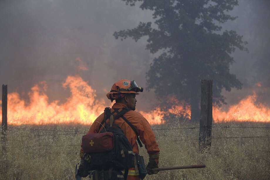 A member of an inmate firefighting crew works on the Bully fire  near Ono, Calif.  A 27-year-old man who was allegedly at an illegal marijuana plot is suspected of starting a wildfire that has burned about 6 square miles of forested land in northern California. Freddie Alexander Smoke III was arrested Saturday, July 12, 2014 and accused of recklessly causing a fire and with marijuana cultivation, both felonies, according to the California Department of Fire and Forestry Protection.   The so-called Bully fire has since grown to 3,700 acres and destroyed six structures, CalFire officials said.  The blaze, which is burning in steep terrain, was just 10 percent contained Sunday morning. Photo: Greg Barnette, Associated Press