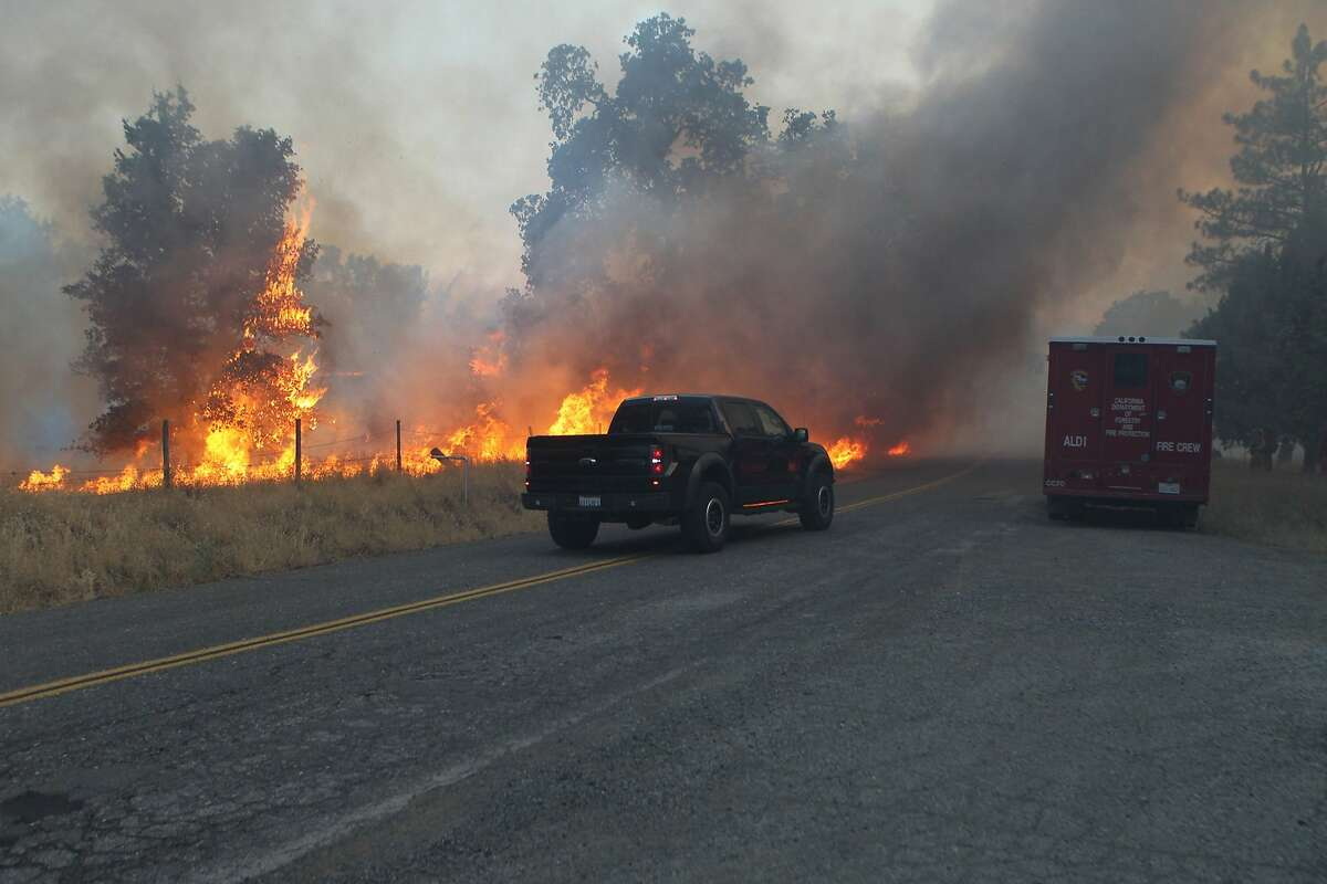 A driver tries to flee the Bully fire Friday, July 11, 2014, off Platino Road near Ono, Calif. Wildfires in rural California burned through 2,000 acres of brush and timberland on Friday, prompting some evacuations, but no homes were threatened, officials said.