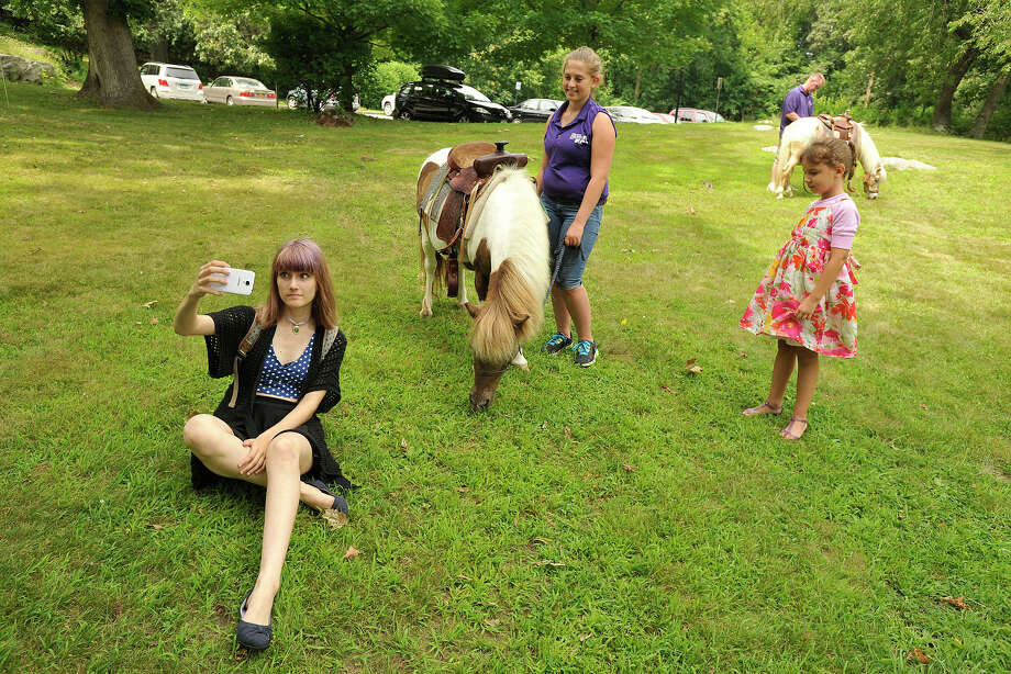 "Dana Alquate, left, takes a selfie with a pony in the background as her sister, Elena Lilu, right, and Becca O'Hara look on during Family Day at the Bruce Museum in Greenwich, Conn., on Sunday, July 13, 2014. The museum had Chinese-inspired events to go with its exhibit, ""Tale of Two Cities: New York & Beijing"" with horses to demonstrate that, according to the Chinese zodiac, this year is the Year of the Horse. Photo: Jason Rearick / Stamford Advocate"