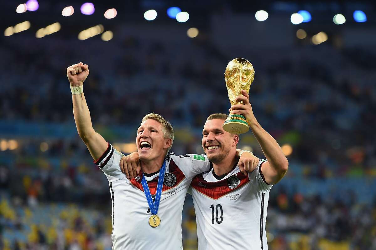 RIO DE JANEIRO, BRAZIL - JULY 13: Bastian Schweinsteiger and Lukas Podolski of Germany celebrate with the World Cup trophy after defeating Argentina 1-0 in extra time during the 2014 FIFA World Cup Brazil Final match between Germany and Argentina at Maracana on July 13, 2014 in Rio de Janeiro, Brazil. (Photo by Laurence Griffiths/Getty Images)
