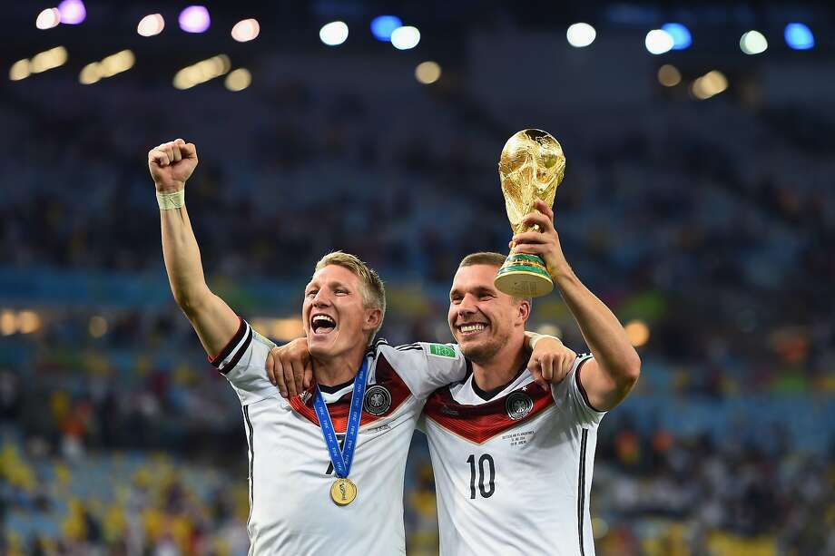 Bastian Schweinsteiger and Lukas Podolski of Germany celebrate with the World Cup trophy after edging Argentina 1-0 in the final in Rio de Janeiro. Photo: Laurence Griffiths, Getty Images