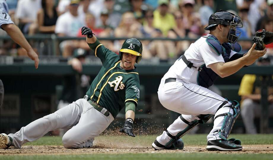 A's shortstop Jed Lowrie scores past Mariners catcher Mike Zunino with Oakland's first run in the fifth inning. Photo: Elaine Thompson, Associated Press