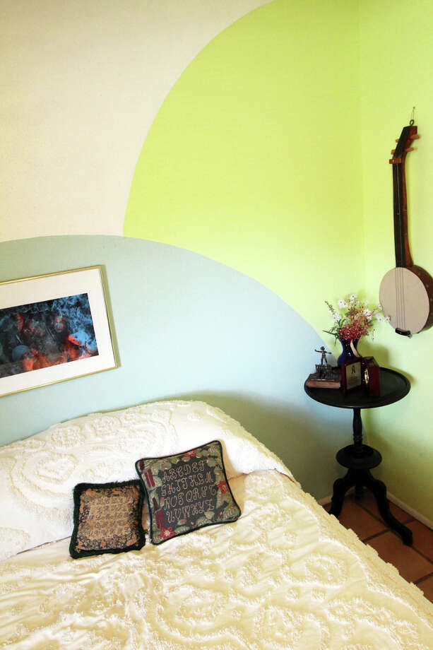 Bonnie Ellison painted circles on the wall of the guest room. A folk art banjo by Lester Lay of Kirksville, Missouri, hangs on a wall in the corner. Embroidered alphabet pillows rest on the bed. Photo: Danny Warner, Danny Warner / For The Express-News