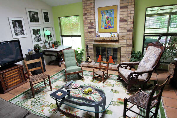 Bonnie Ellison�s grandmother�s thread spool cabinet provides a base for the television at left, antique rockers (also from her grandmother)and Amish chairs circle the glass-topped coffee table in the living room.