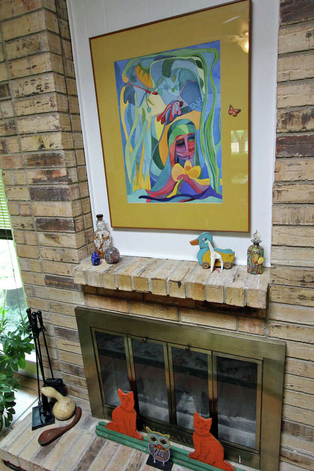 A painting by a Missouri artist hangs above the fireplace in Bonnie Ellison's home. The folk art duck and cats were made by Lester Lay of Kirksville, Missouri, Ellison's hometown. Photo: Danny Warner, Danny Warner / For The Express-News