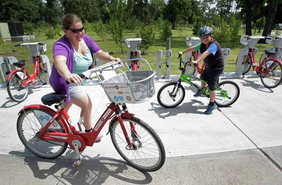 Crystal Humble, of Douglas, Arizona, returns a B-Cycle after riding with her son, Landen, 8, in Hermann Park on Friday. Photo: Melissa Phillip, Staff / © 2014  Houston Chronicle