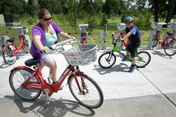 Crystal Humble, of Douglas, Arizona, returns a B-Cycle after riding with her son, Landen, 8, in Hermann Park on Friday.