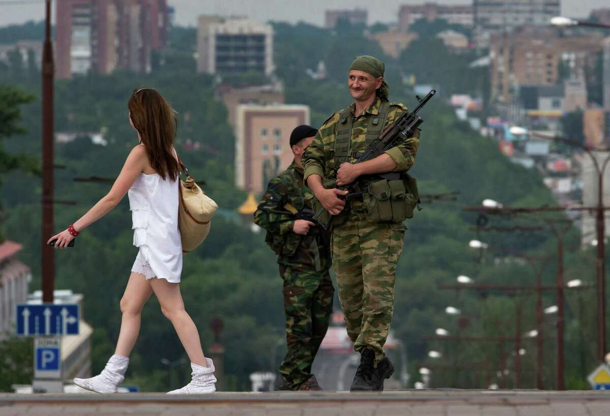 A woman walks past Donetsk People's Republic fighters standing guard in the city of Donetsk, eastern Ukraine Sunday, July 13, 2014.