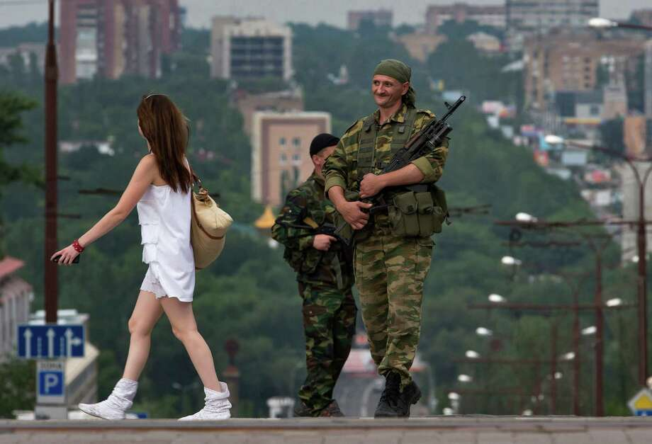 A woman walks past Donetsk People's Republic fighters standing guard in the city of Donetsk, eastern Ukraine Sunday, July 13, 2014. Photo: Dmitry Lovetsky, AP / AP