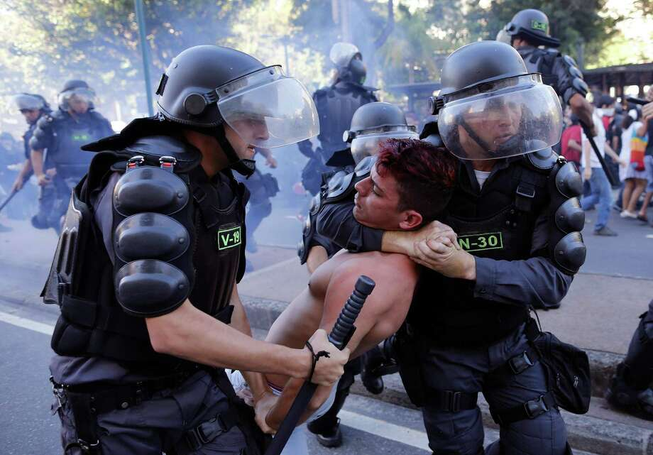 Police arrest a demonstrator during an Anti-World Cup protest near Maracana stadium where the final World Cup game is taking place in Rio de Janeiro, Brazil, Sunday, July 13, 2014. For the final match between Argentina and Germany, authorities deployed the largest security detail in Brazil's history. Photo: Leo Correa, AP / AP2014