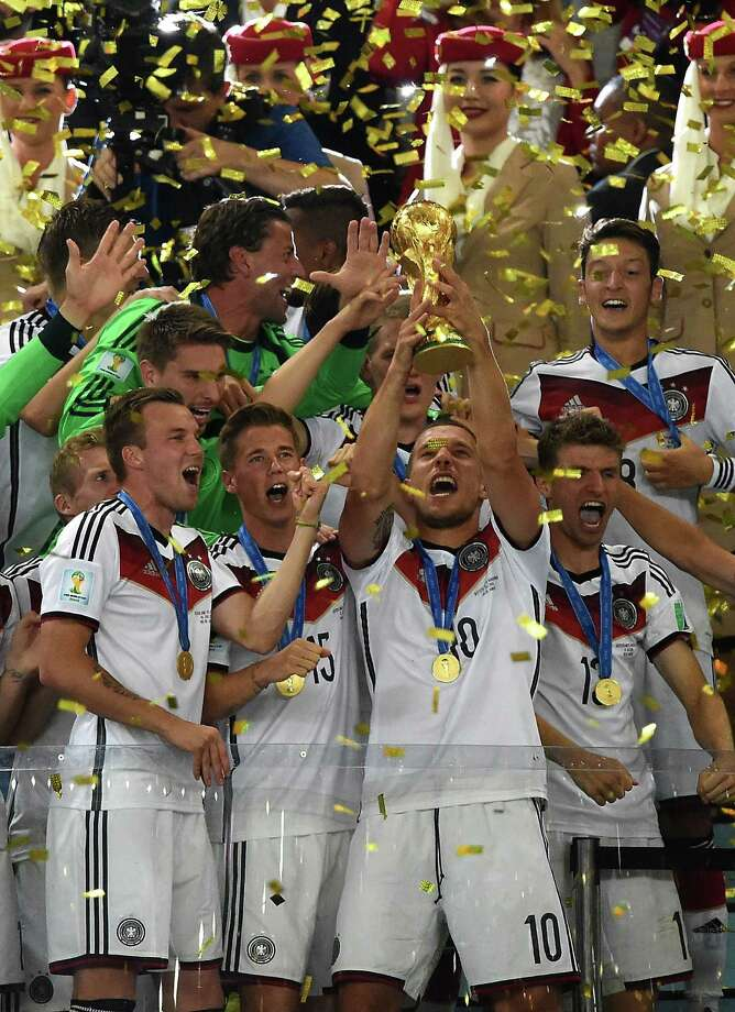 Germany's forward Lukas Podolski (front R) and team-mates celebrate with the World Cup trophy after they won the 2014 FIFA World Cup final football match between Germany and Argentina 1-0 following extra-time at the Maracana Stadium in Rio de Janeiro, Brazil, on July 13, 2014.         AFP PHOTO / PEDRO UGARTEPEDRO UGARTE/AFP/Getty Images ORG XMIT: 491717433 Photo: PEDRO UGARTE / AFP