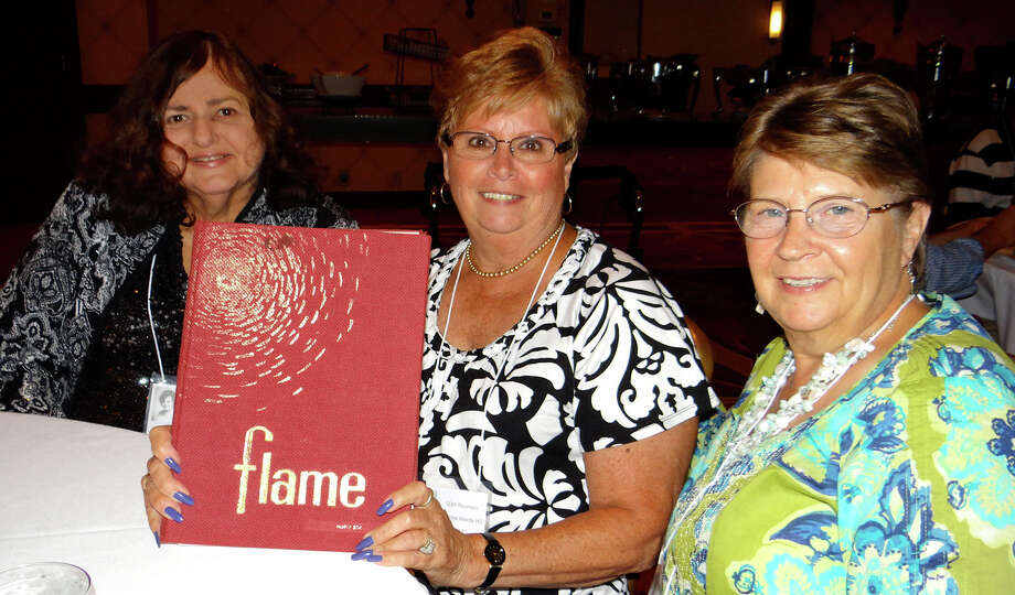 Andrew Warde High School Class of 1964 graduates Kathy Tovish, Virginia Bok and Carol Galemba leaf through a yearbook at their 50th reunion Saturday evening. Photo: Mike Lauterborn / Fairfield Citizen