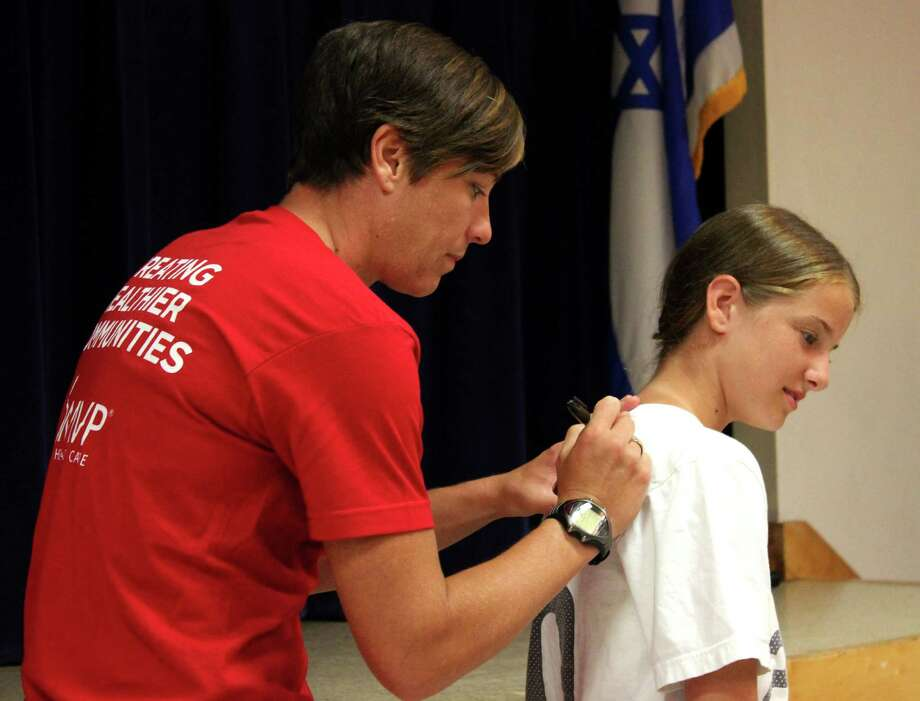 Abby Wambach, left, signs the shirt of 13-year-old Chloe Lovely, right, of Latham on Sunday, July 13, 2014, at the Schenectady JCC in Schenectady N.Y. (Selby Smith/Special to the Times Union) Photo: Selby Smith / 00027750A
