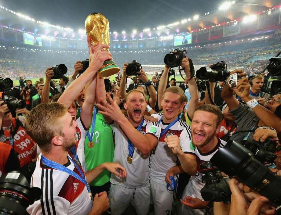 German players including Benedikt Hoewedes (center) display the World Cup trophy after defeating Argentina 1-0 in extra time Sunday in Rio de Janeiro. The title is the nation's first since 1990, when then-West Germany defeated Argentina. Photo: Martin Rose / Getty Images / 2014 Getty Images
