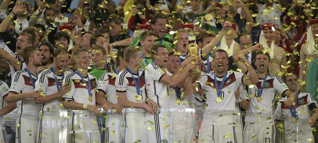 Germany's forward Lukas Podolski (3R) holds The World Cup as he celebrates with teammates after his team's victory in the final football match between Germany and Argentina for the FIFA World Cup at The Maracana Stadium in Rio de Janeiro on July 13, 2014.   AFP PHOTO / JUAN MABROMATAJUAN MABROMATA/AFP/Getty Images Photo: AFP/Getty Images / AFP