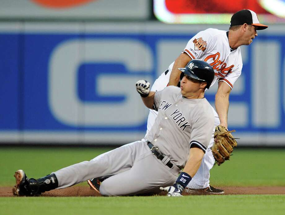 Baltimore Orioles shortstop J.J. Hardy, right, tags out New York Yankees Mark Teixeira, on a throw from Nick Markakis  in the first inning of a baseball game, Sunday, July 13, 2014, in Baltimore.(AP Photo/Gail Burton) ORG XMIT: MDGB106 Photo: Gail Burton / FR4095 AP