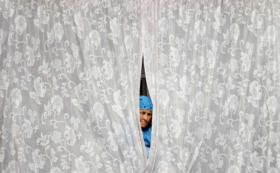 A Kashmiri woman watches from behind a curtain of a window in Srinagar, India, Sunday, July 13, 2014. Martyr's Day is observed on July 13 in Kashmir traditionally by both separatists and pro-Indian Kashmiris to commemorate the day in 1931 when the region's Hindu king ordered more than 20 Kashmiri Muslims executed in a bid to put down an uprising. On Sunday, separatist groups called for strike in memory of the day. (AP Photo/Mukhtar Khan) Photo: Mukhtar Khan, Associated Press