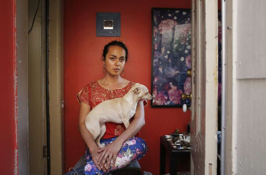 With his dog Callie on his lap, artist Jean Franco Pilas honors Frida Kahlo in his San Francisco home. Photo: Mike Kepka, The Chronicle