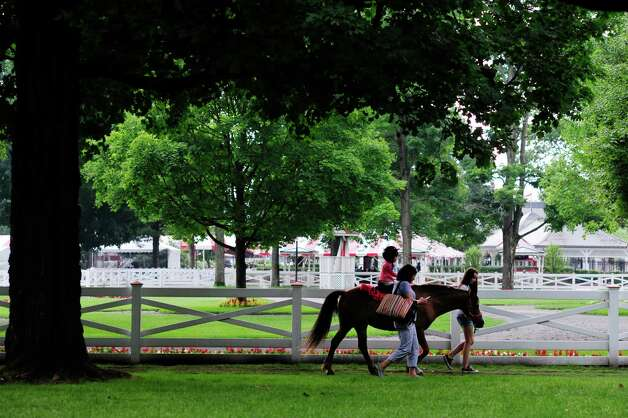 Doris Chin of Clifton Park walks along as her daughter, Alyssa Smith, 3, ride a pony at the Open House for the Saratoga Race Course on Sunday, July 13, 2014, in Saratoga Springs, N.Y.  (Paul Buckowski / Times Union) Photo: Paul Buckowski / 00027731A