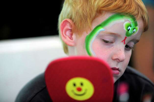 Anthony Nicoletti, 7, of Kingston checks out painted rattle snake on his face at the Open House for the Saratoga Race Course on Sunday, July 13, 2014, in Saratoga Springs, N.Y.  Members of the Electric City Clown Alley painted the faces for children.  (Paul Buckowski / Times Union) Photo: Paul Buckowski / 00027731A