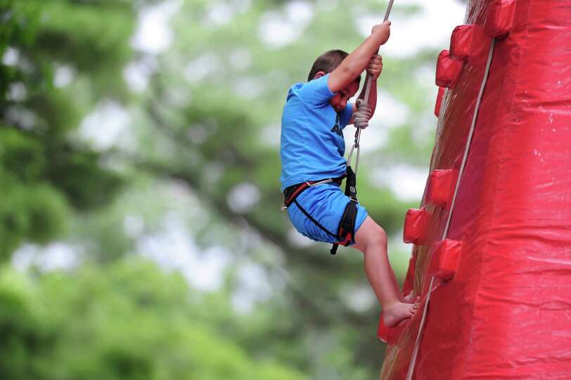 Jaden Geno, 4, of Ballston Spa climbs an inflatable wall at the Open House for the Saratoga Race Cou