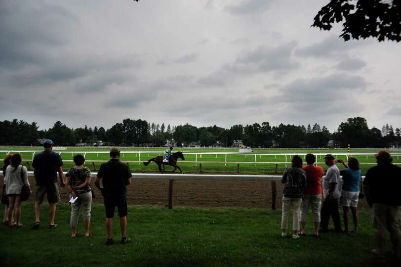 A jockey aboard a horse rides along the Oklahoma Training Track at the Open House for the Saratoga R
