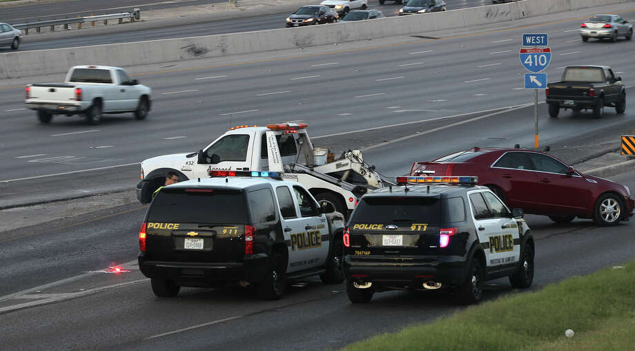 A Cadillac Seville is towed away Monday July 14, 2014 on the westbound Loop 410 access road after it struck a woman crossing lanes at about 4:52 a.m.. San Antonio police sergeant James Lint said a female passenger in the vehicle exited the car and crossed several lanes of traffic when the car looped back around on the highway and struck her. Lint said the people in the same vehicle were involved in a disturbance at a nearby apartment complex earlier. Lint said the woman is in critical condition at University Hospital. Photo: JOHN DAVENPORT, San Antonio Express-News / ©San Antonio Express-News/John Davenport
