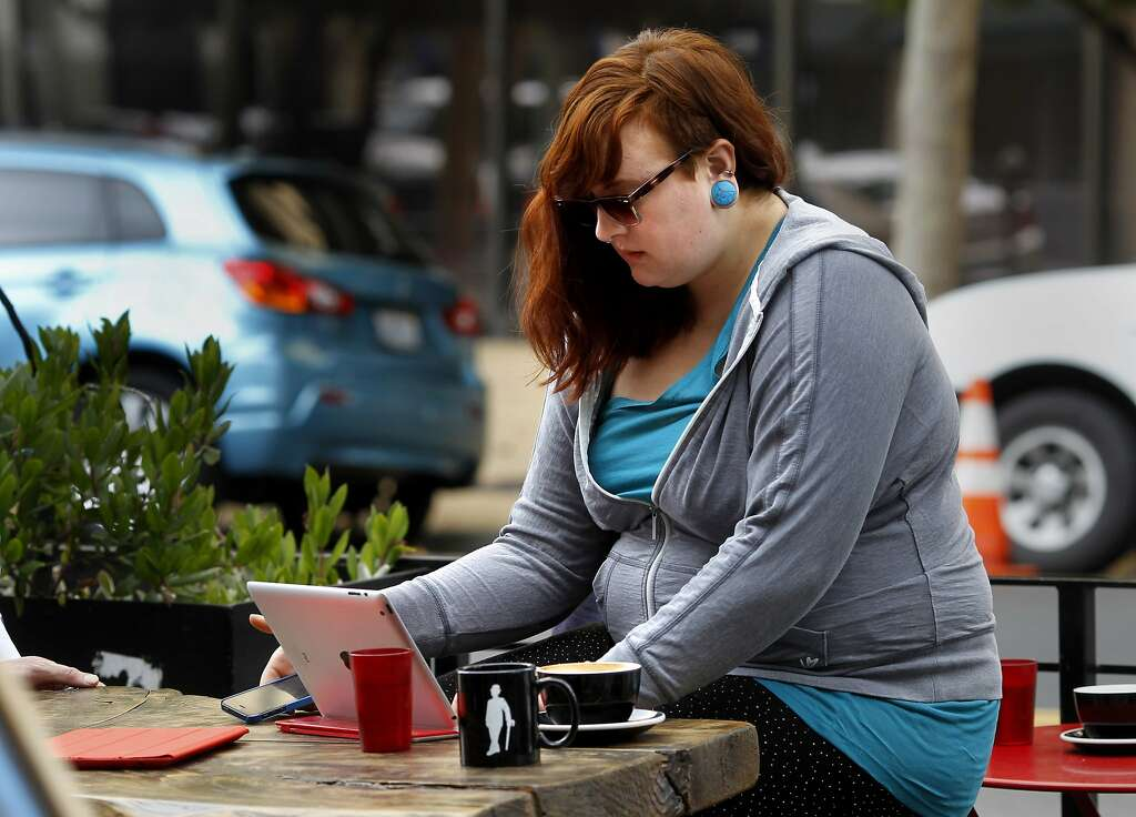 Jolene Parton works on her computer and checks messages at an outdoor  coffee shop on Grand