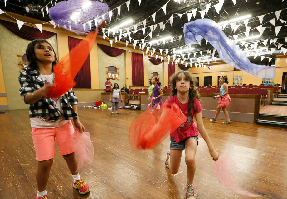 Alani Nicole Arredondo (left) and Emi Ramirez, both 9, learn to juggle scarves at the  summer circus camp at Guadalupe Theater. There, Pam and Alberto Ramirez Jr. have been teaching the children circus tricks in the tradition of Mexican carpas. Photo: Marvin Pfeiffer / EN Communities / EN Communities 2014