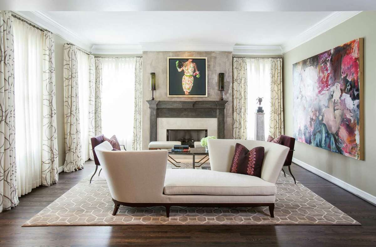 In the formal living room, a téªte-é-téªte from Donghia and soft purple details inspired by the Angela Fraleigh painting on the wall.