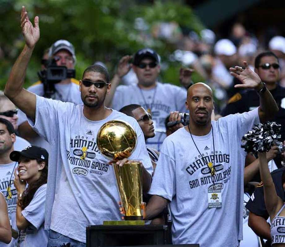 FOR METRO - Spurs' forward Tim Duncan (21) and forward Bruce Bowen (12) wave to fans during the victory parade Sunday June 17, 2007, at the River Center Lagoon (EDWARD A. ORNELAS/STAFF) Photo: EDWARD A. ORNELAS, SAN ANTONIO EXPRESS-NEWS / SAN ANTONIO EXPRESS-NEWS