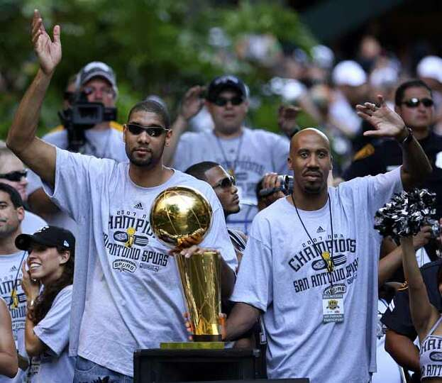 FOR METRO - Spurs' forward Tim Duncan (21) and forward Bruce Bowen (12) wave to fans during the vict