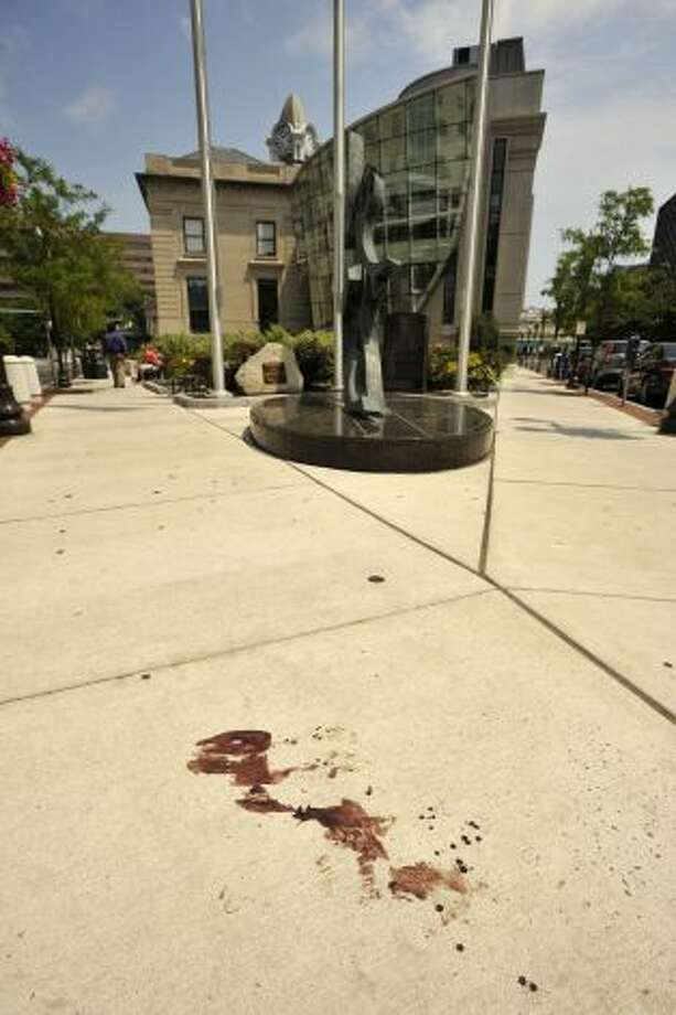 The sidewalk at the corner of Main and Bank Streets where a witness said he saw a victim retreat to after being shot in Stamford, Conn., on Sunday, July 13, 2014. In the early morning hours of Sunday police say Dayron Wills opened fire with a handgun outside a Columbus Park night club striking five people. The five victims were said to not have life-threatening injuries. Photo: Jason Rearick, Stamford Advocate