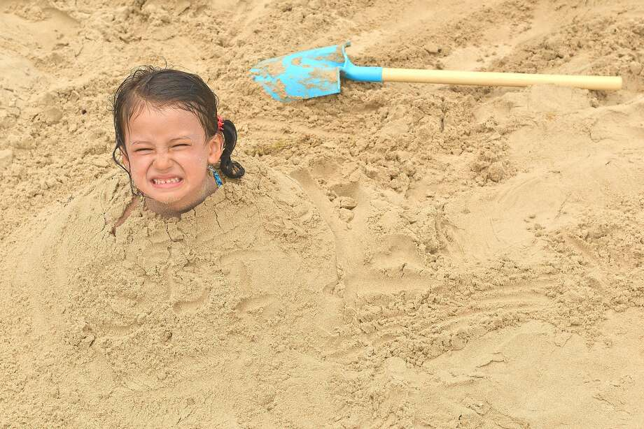Your brother did this, didn't he? Four-year-old Magaly Copus of Oklahoma is buried in sand up to her 