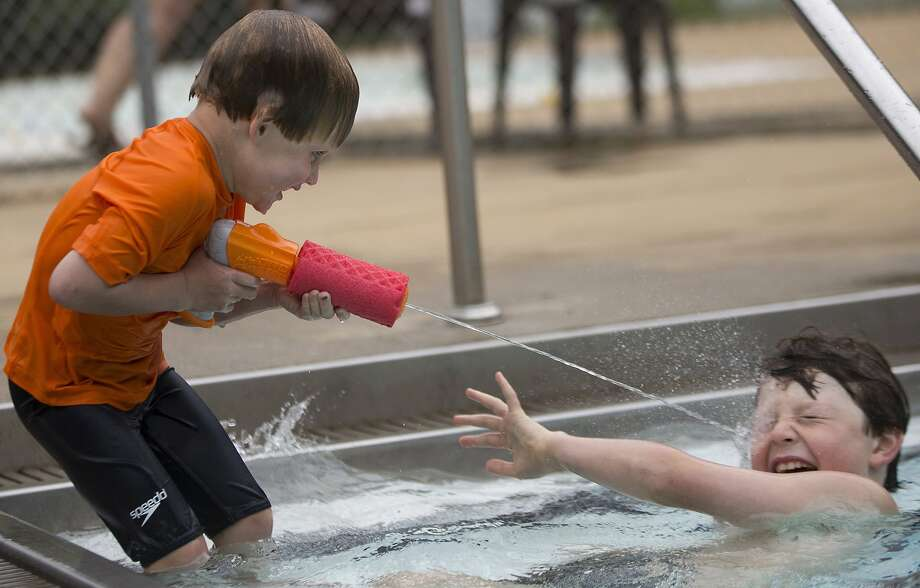 Why they call little brothers 'Squirt':Four-year-old Sam Askew shoots his older brother, Charlie, 8,  right in the eye at Ridge Road Pool in Raleigh, N.C. Photo: Sarah Shaw, Associated Press