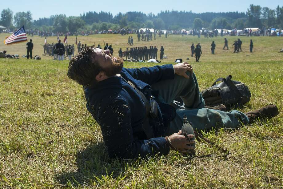 Groaning in pain adds to the realism: Christopher Gove pretends to be wounded during a reenactment of the Siege of Petersburg, near Chehalis, Wash., far from the original battle. Gove, portraying a member of 20th Maine Company F, said he felt it was more accurate to be wounded in the Civil War reenactment than to just play dead. Photo: Pete Caster, Associated Press