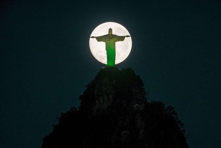 Amid Brazilian disappointment, the World Cup comes to a close:The moon descends behind the statue of Christ the Redeemer, lit with the colors of the Brazilian 
