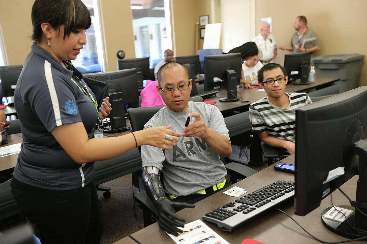 Bexar Bibliotech Technology Assistant Lynette Barrera, left, helps out Staff Sgt. Nhut Nguyen, of Boston, sign up for the digital library at the Warrior and Family Support Center of Joint Base San Antonio-Fort Sam Houston, Monday, July 14, 2014. Bexar County opened the digital library at the center and will make available its content to military personnel and families of personnel under going treatment and recovery at Brooke Army Medical Center. On the right is Tung Mai, Nguyen's brother visiting from Boston.