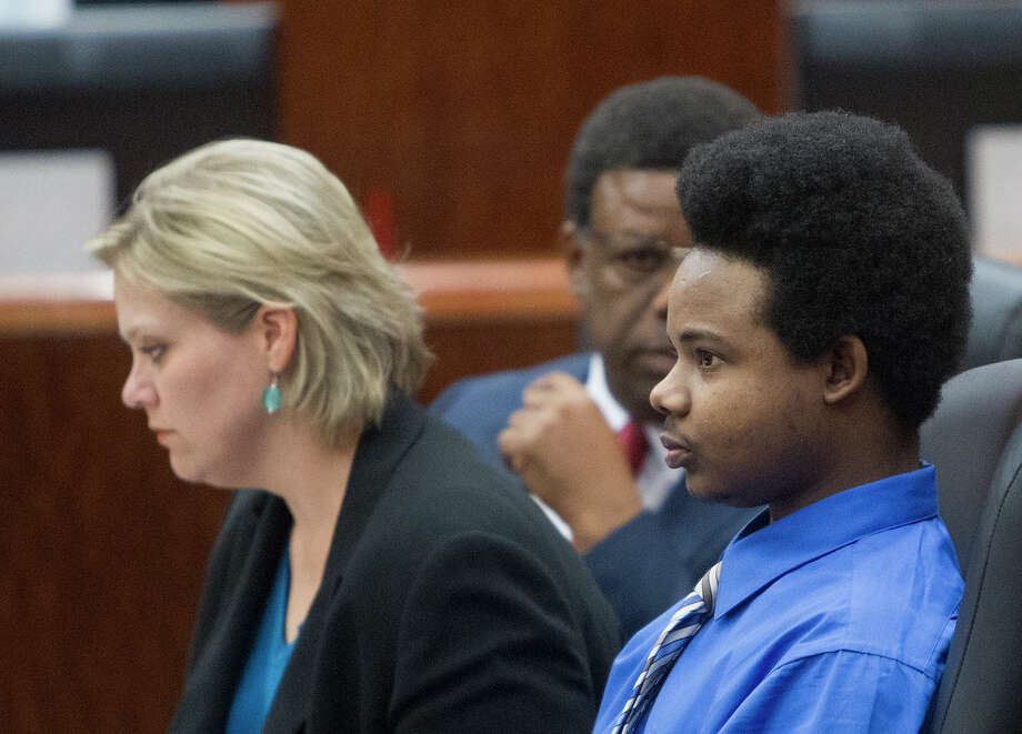 Harlem Lewis, right, sits with his attorneys before his trial begins at the Harris County Criminal Courthouse, Monday, July 14, 2014, in Houston. Lewis is accused of fatally shooting Bellaire police corporal Jimmie Norman and Terry Taylor, a bystander who had to come to Norman's aid, on December 24, 2012. He could face the death penalty. Photo: Cody Duty, Houston Chronicle / © 2014 Houston Chronicle