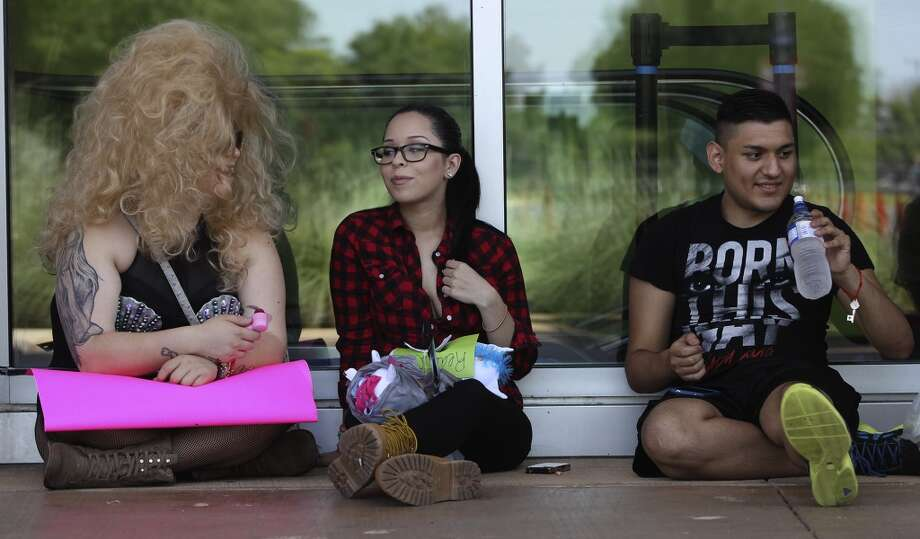 Brooklyn Mixon (left), Karla Ramirez (center) and Jose Chavez (right) wait in line Monday July 14, 2014 at the AT&T Center for Lady Gaga tickets. The concert is tonight at 7:30 p.m. . Photo: San Antonio Express-News