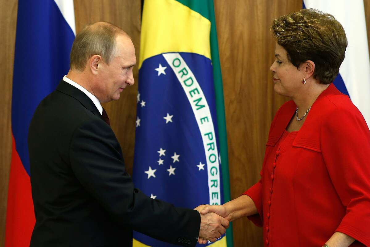 Russia's President Vladimir Putin, left, shakes hands with Brazil's President Dilma Rousseff during an agreement signing ceremony at Planalto Presidential Palace in Brasilia, Brazil, Monday, July 14, 2014. Putin is in Brazil to attend a presidential summit of the BRICS group of nations. He was in Rio de Janeiro on Sunday for the World Cup final and ceremonial handover of host duties for soccer's marquee tournament, which next takes place in Russia in 2018. (AP Photo/Eraldo Peres)