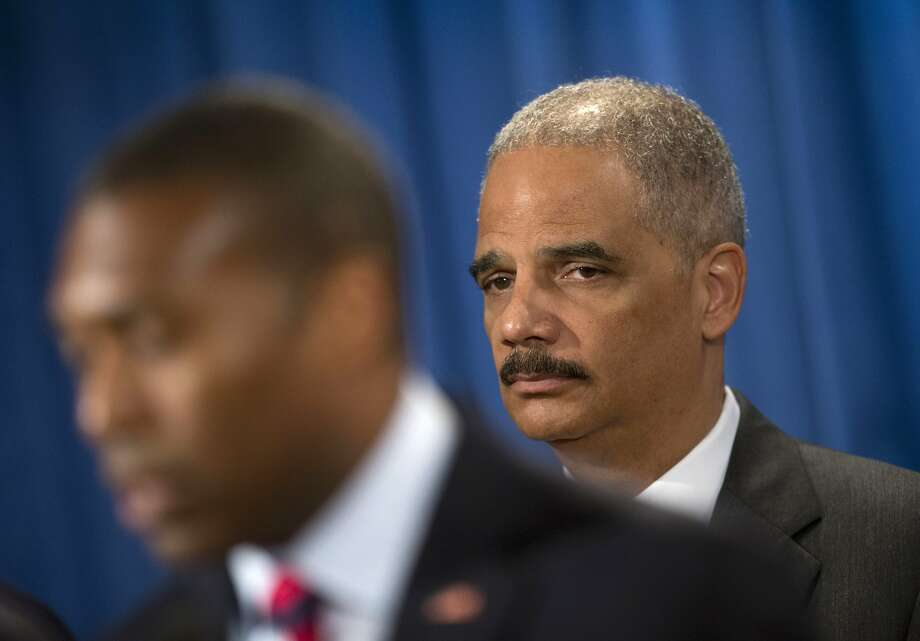 Eric Holder (right) listens as Tony West, the Justice Department's lead negotiator, answers questions. Photo: Pablo Martinez Monsivais, Associated Press